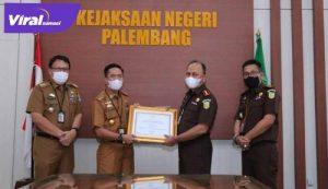 SekdaKota Palembang, Drs. Ratu Dewa, menyerahkan dua piagam penghargaan kepada Jaksa Pengacara Negara Kejari Palembang. FOTO : VIRALSUMSEL.COM